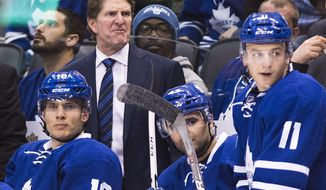 FILE - In this Oct. 25, 2016, file photo, Toronto Maple Leafs head coach Mike Babcock, back, reacts while playing against the Tampa Bay Lightning during the second period of an NHL hockey game in Toronto. The NHL's coaching carousel is paying off for playoff-starved franchises in Toronto, Edmonton and Columbus. With the season wrapping up on Sunday, the Maple Leafs' Mike Babcock, Oilers' Todd McLellan and Blue Jackets' John Tortorella have emerged as coach of the year candidates. (Nathan Denette/The Canadian Press via AP, File)