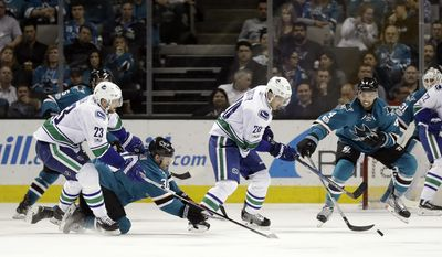Vancouver Canucks center Brandon Sutter (20) controls the puck as San Jose Sharks' Brenden Dillon (4) and Jannik Hansen, second from left, defend during the second period of an NHL hockey game Tuesday, April 4, 2017, in San Jose, Calif. (AP Photo/Marcio Jose Sanchez)