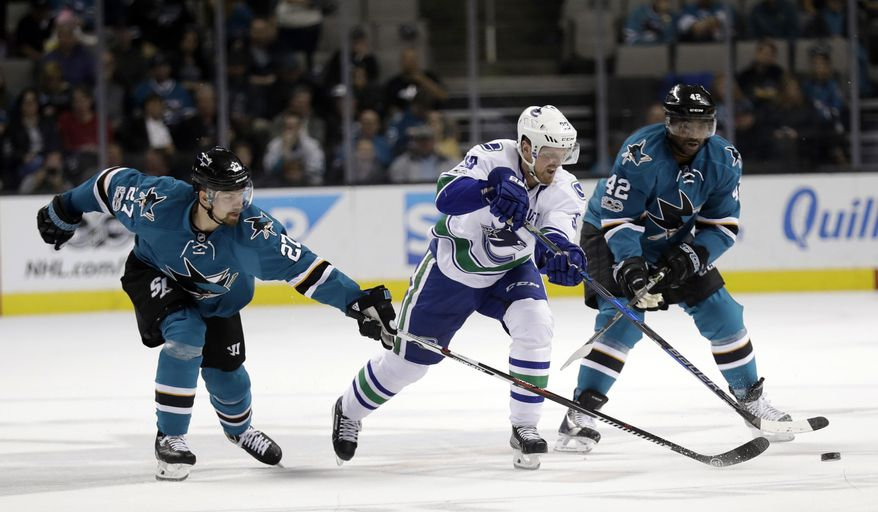Vancouver Canucks' Henrik Sedin, center, is defended by San Jose Sharks' Joonas Donskoi (27) and Joel Ward (42) during the first period of an NHL hockey game Tuesday, April 4, 2017, in San Jose, Calif. (AP Photo/Marcio Jose Sanchez)