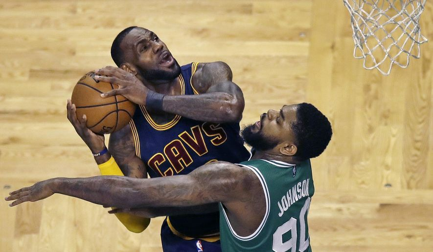 Cleveland Cavaliers forward LeBron James, left, drives to the basket against Boston Celtics forward Amir Johnson (90) during the first quarter of an NBA basketball game in Boston, Wednesday, April 5, 2017. (AP Photo/Charles Krupa)