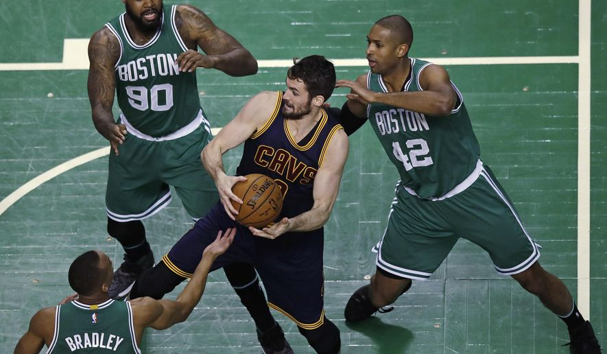 Cleveland Cavaliers forward Kevin Love, center is surrounded by Boston Celtics players as he grabs a rebound during the first quarter of an NBA basketball game in Boston, Wednesday, April 5, 2017. (AP Photo/Charles Krupa)
