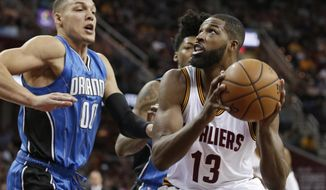 This Tuesday, April 4, 2017 photo shows Cleveland Cavaliers' Tristan Thompson (13) drives to the basket against Orlando Magic's Aaron Gordon (00), during the first half of an NBA basketball game, in Cleveland. Thompson sprained his right thumb and will miss Cleveland's first-place showdown with Boston on Wednesday night. Thompson got hurt during the third quarter of Tuesday's win over Orlando and did not travel with the team to Boston. (AP Photo/Tony Dejak)