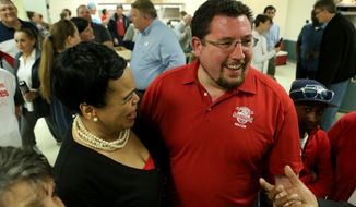 Ferguson mayor James Knowles III, center, celebrates his election victory with his campaign supporters at the Lion's Club in Ferguson, Mo., Tuesday, April 4, 2017. Ferguson, Missouri's top elected official in the tumultuous 32 months since the fatal police shooting of Michael Brown won another three-year term Tuesday. (David Carson/St. Louis Post-Dispatch via AP)