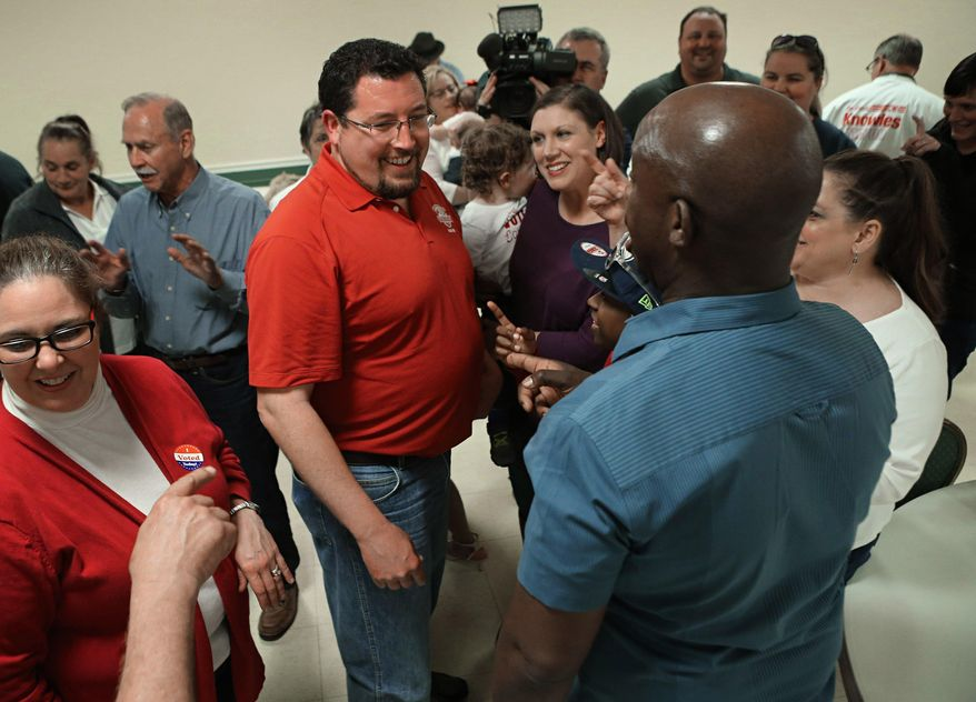 Ferguson mayor James Knowles III, center, celebrates his election victory with his campaign supporters at the Lion's Club in Ferguson, Mo., Tuesday, April 4, 2017. Ferguson, Missouri's top elected official in the tumultuous 32 months since the fatal police shooting of Michael Brown won another three-year term Tuesday. (David Carson /St. Louis Post-Dispatch via AP)