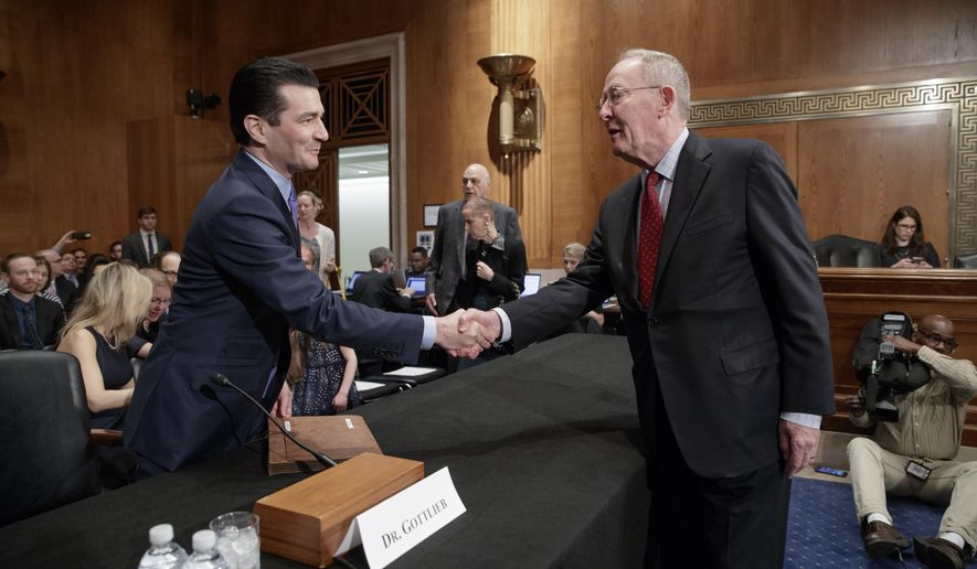 Dr. Scott Gottlieb, left, President Donald Trump's nominee to head the Food and Drug Administration (FDA), is greeted by Senate Health, Education, Labor, and Pensions Committee Chairman Sen. Lamar Alexander, R-Tenn., as he arrives for his confirmation hearing on Capitol Hill in Washington, Wednesday, April 5, 2017. (AP Photo/J. Scott Applewhite)