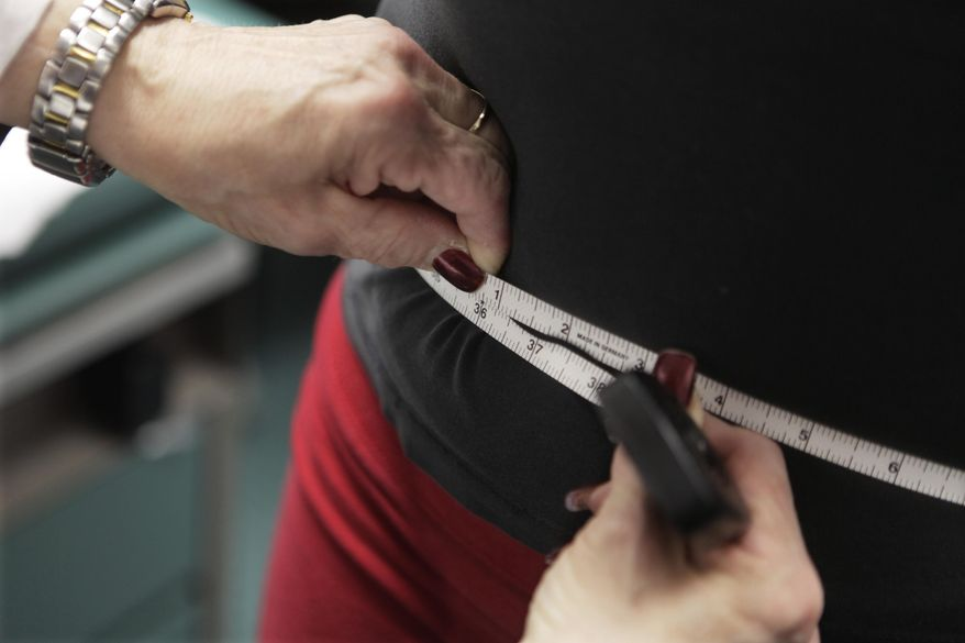 In this Jan. 20, 2010, file photo, a waist is measured during an obesity prevention study in Chicago. (AP Photo/M. Spencer Green, File) **FILE**