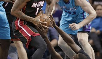 Miami Heat's Rodney McGruder, left, grabs a loose ball as Charlotte Hornets' Michael Kidd-Gilchrist, bottom, and Cody Zeller, right, defend during the first half of an NBA basketball game in Charlotte, N.C., Wednesday, April 5, 2017. (AP Photo/Chuck Burton)