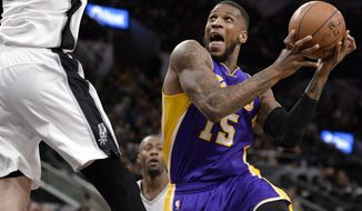 Los Angeles Lakers forward Thomas Robinson (15) attempts to shoot against San Antonio Spurs forward Davis Bertans, of Latvia, during the first half of an NBA basketball game, Wednesday, April 5, 2017, in San Antonio. (AP Photo/Darren Abate)
