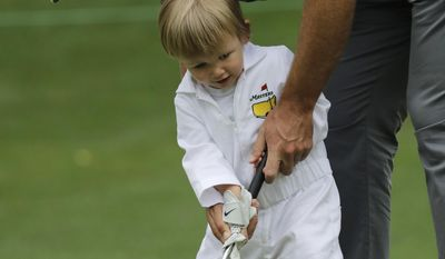Kevin Chappell helps his son Wyatt putt on the second hole during the par three competition at the Masters golf tournament Wednesday, April 5, 2017, in Augusta, Ga. (AP Photo/Charlie Riedel)
