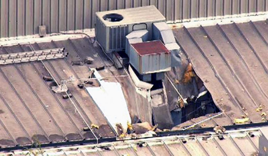 This Monday, April 3, 2017 photo from video by KMOV shows damage to the roof of a laundry business in St. Louis after a boiler exploded at a nearby box company and flew before crashing through the roof. Authorities said several people were killed as a result of the explosion. (KMOV via AP)