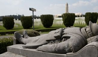 The statue of a French Poilu lies in front of the Douaumont Ossuary in Verdun, France. World War I brought unprecedented trench warfare to northern France and Belgium. The toll of dead was so immense in the Verdun region that soldiers from both sides were buried together in the ossuary. (Associated Press/File)