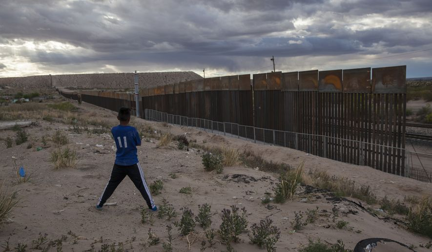 A youth looks at a new, taller fence being built along U.S.-Mexico border, replacing the shorter, gray metal fence in front of it, in the Anapra neighborhood of Ciudad Juarez, Mexico, across the border from Sunland Park, New Mexico, on March 29, 2017. (Associated Press) **FILE**