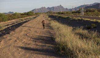 Mark Hainds, a 48-year-old junior community college forestry professor from Andalusia, Alabama, walks about 3 miles from his stopping point, near Why, Ariz., Monday, April 3, 2017. (AP Photo/Rodrigo Abd)