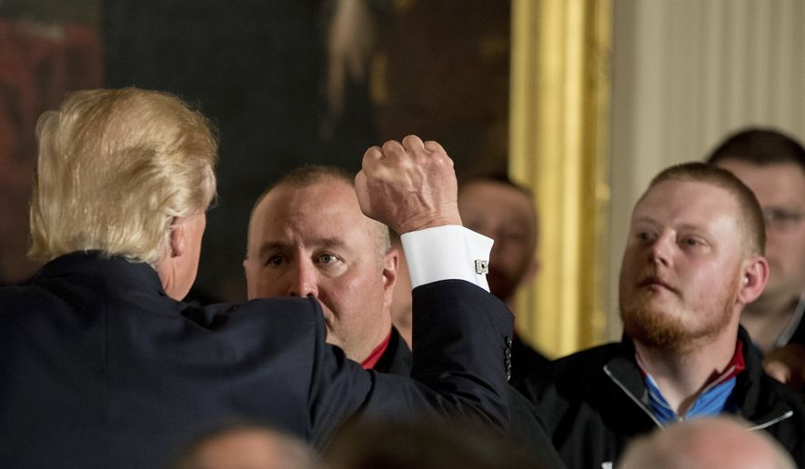 President Donald Trump raises a fist as he greets servicemen at a Wounded Warrior Project Soldier Ride event in the East Room of the White House in Washington, Thursday, April 6, 2017. (AP Photo/Andrew Harnik)