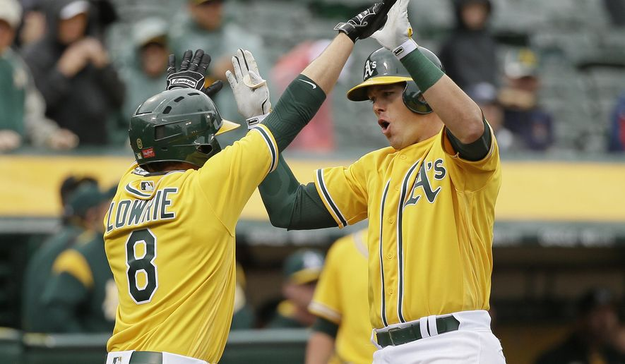 Oakland Athletics' Ryon Healy, right, is greeted by teammate Jed Lowrie, left, after hitting a two-run home run off Los Angeles Angels starting pitcher Tyler Skaggs in the third inning of a baseball game Thursday, April 6, 2017, in Oakland, Calif. (AP Photo/Eric Risberg)