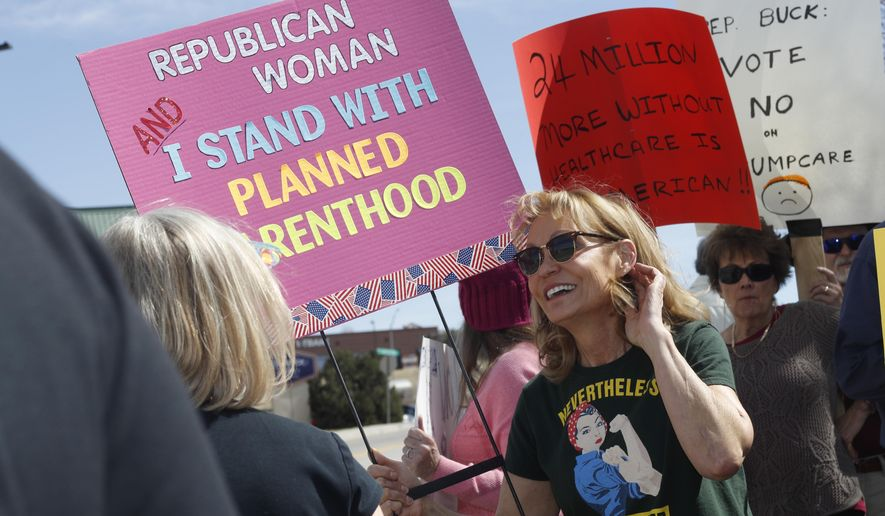 In this Wednesday, March 22, 2017 photo, Carolyn Williamson waves a placard in support of Planned Parenthood as she joins other protesters against the failed Republican health care act in a demonstration outside the office of U.S. Rep. Ken Buck in Castle Rock, Colo. A Republican until the past presidential election, Williamson has joined a conservative group against the policies of President Donald Trump. (AP Photo/David Zalubowski)