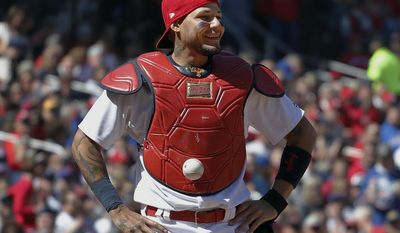 St. Louis Cardinals catcher Yadier Molina stands with his hands on his hips as a ball is somehow stuck to his chest protector during the seventh inning of a baseball game against the Chicago Cubs on Thursday, April 6, 2017, in St. Louis. The ball was stuck to Molina's chest protector on a dropped third strike allowing the Cubs' Matt Szczur to reach first base when Molina couldn't find the ball. (AP Photo/Jeff Roberson)