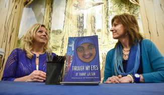 """In a Saturday, April 1, 2017 photo, author Tammy Wilson, left, and illustrator Jill Dubbeldee Kuhn talk about their book, """"Through My Eyes,"""" during an event at Barnes and Noble in St. Cloud, Minn. (Dave Schwarz/The St. Cloud Times via AP)"""