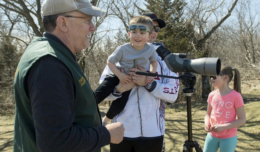 "ADVANCE FOR MONDAY, APRIL 10, 2017- In this Saturday, April 1, 2017 photo, Minneopa State Park volunteer Tim Pulis, left, talks with Lennox Tofte, 3, after showing him bison on the prairie at the park through a spotting scope, while Lennox's dad Matt holds him Saturday, April 1, 2017, near Mankato, Minn. Pulis is among the volunteer ""bison ambassadors"" at the park who answer questions for the public. (Jackson Forderer/The Free Press via AP)"