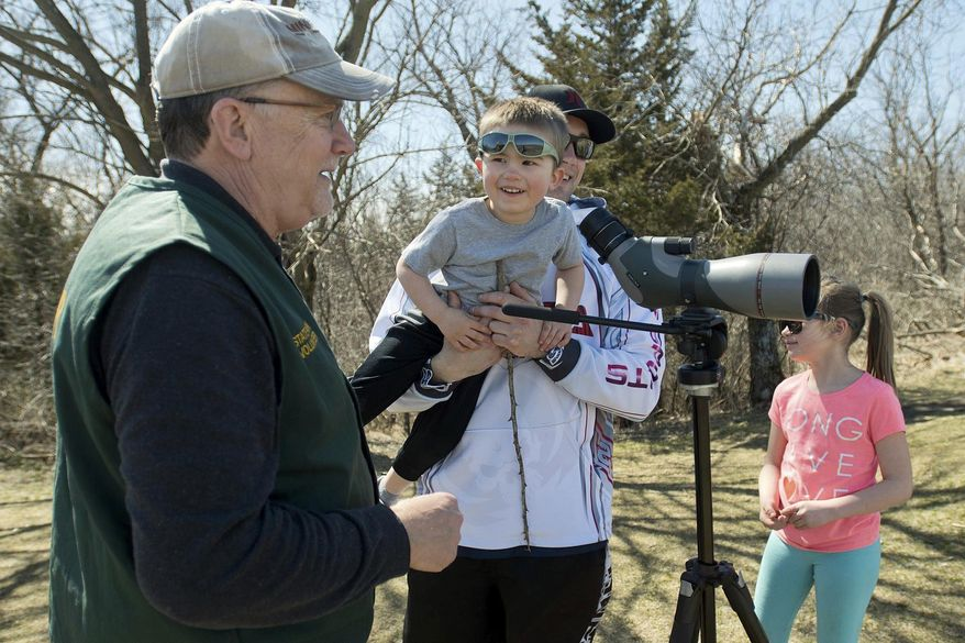 """ADVANCE FOR MONDAY, APRIL 10, 2017- In this Saturday, April 1, 2017 photo, Minneopa State Park volunteer Tim Pulis, left, talks with Lennox Tofte, 3, after showing him bison on the prairie at the park through a spotting scope, while Lennox's dad Matt holds him Saturday, April 1, 2017, near Mankato, Minn. Pulis is among the volunteer """"bison ambassadors"""" at the park who answer questions for the public. (Jackson Forderer/The Free Press via AP)"""