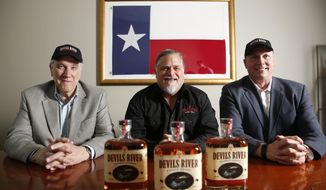 From left, Devils River Whiskey founders, Rick Leeper, Mike Cameron and Mike Beucler pose for a photograph at their bottling facility in Dallas on March 22, 2017.  Devils River is the latest to join North Texas' burgeoning small-batch distillery scene, which is gaining momentum like the craft brewery movement before it. Between 1995 and 2008, the Texas Alcoholic Beverage Commission issued 10 licenses to spirits manufacturers.  (Rose Baca/The Dallas Morning News via AP)