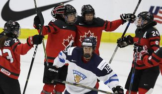 Finland forward Tanja Niskanen (19) skates away as Canada forward Rebecca Johnston, second from left, is congratulated by teammates after her goal during the second period of an IIHF women's world hockey championship semifinal game Thursday, April 6, 2017, in Plymouth, Mich. (AP Photo/Carlos Osorio)