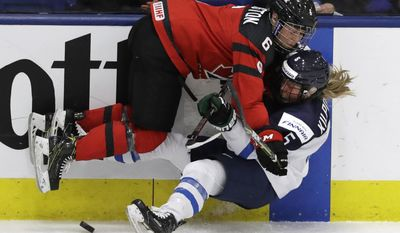 Canada forward Rebecca Johnston (6) hits Finland defender Anna Kilponen (5) during the second period of an IIHF women's world hockey championship semifinal game Thursday, April 6, 2017, in Plymouth, Mich. (AP Photo/Carlos Osorio)