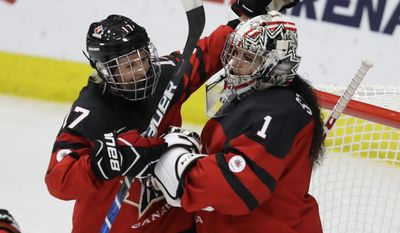Canada forward Bailey Bram (17) pats goalie Shannon Szabados after the third period of an IIHF women's world hockey championship semifinal game against Finland on Thursday, April 6, 2017, in Plymouth, Mich. (AP Photo/Carlos Osorio)