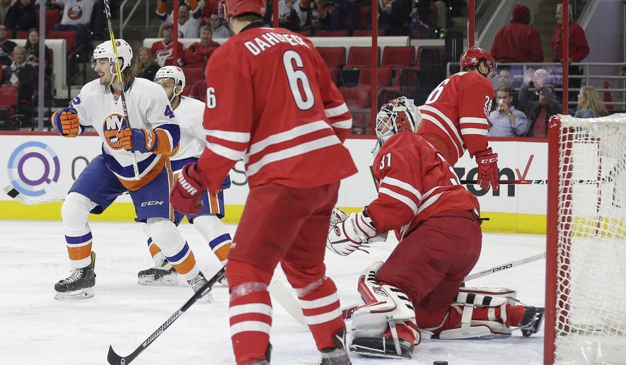 New York Islanders' Scott Mayfield, left, reacts after scoring against Carolina Hurricanes goalie Eddie Lack (31), of Sweden, as Hurricanes' Klas Dahlbeck (6), of Sweden, watches during the first period of an NHL hockey game in Raleigh, N.C., Thursday, April 6, 2017. (AP Photo/Gerry Broome)