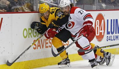 """FILE - In this Sunday, April 2, 2017, file photo, Carolina Hurricanes' Justin Faulk (27) checks Pittsburgh Penguins' Josh Archibald (45) into the boards during the second period of an NHL hockey game in Pittsburgh. Players' anger over the NHL's decision not to go to the 2018 Olympics could foreshadow another ugly labor fight in a few years. The league offered an agreement to go to Pyeongchang next year in exchange for extending the CBA until 2025, but players rejected what Faulk likened to a """"ridiculous"""" bad trade. (AP Photo/Gene J. Puskar, File)"""