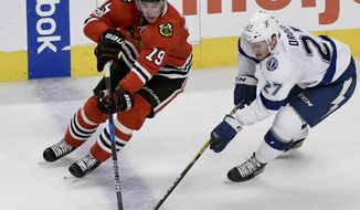 FILE - In this Tuesday, Jan. 24, 2017, file photo, Chicago Blackhawks center Jonathan Toews (19) and Tampa Bay Lightning left wing Jonathan Drouin (27) fight for the puck during the third period of an NHL hockey game in Chicago. Players' anger over the NHL's decision not to go to the 2018 Olympics could foreshadow another ugly labor fight in a few years. If another labor war is brewing for the NHL, Toews won't be caught off-guard. The Blackhawks captain shrugged when asked this past week about the bad, old days, like the lockout that wiped out the 2004-05 season and the delayed beginning of the 2012-13 season not all that long ago. (AP Photo/Matt Marton, File)