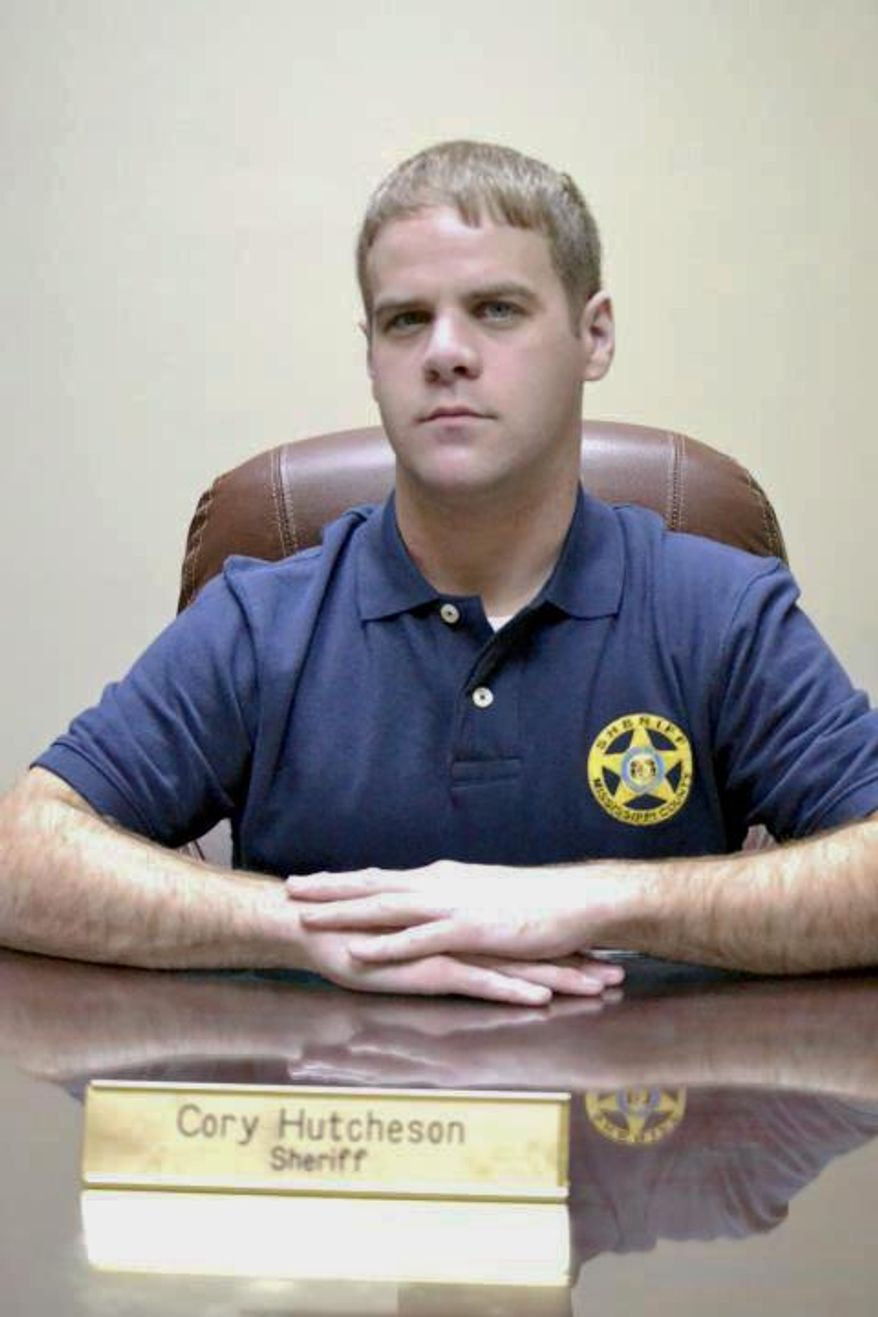 In this undated photo, Mississippi County Sheriff Cory Hutcheson sits behind his desk at the Mississippi County Detention Center in Charleston, Mo. Hutcheson, a southeast Missouri sheriff, was charged Wednesday, April 5, 2017, with assault for allegedly handcuffing a 77-year-old woman with enough force to cause her to have a heart attack. (Leonna Heuring/Standard via AP)