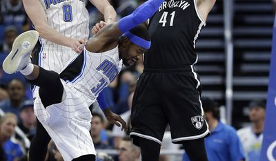 Brooklyn Nets' Justin Hamilton (41) catches a high pass in front of Orlando Magic's Mario Hezonja (8) and Terrence Ross (31) during the first half of an NBA basketball game, Thursday, April 6, 2017, in Orlando, Fla. (AP Photo/John Raoux)