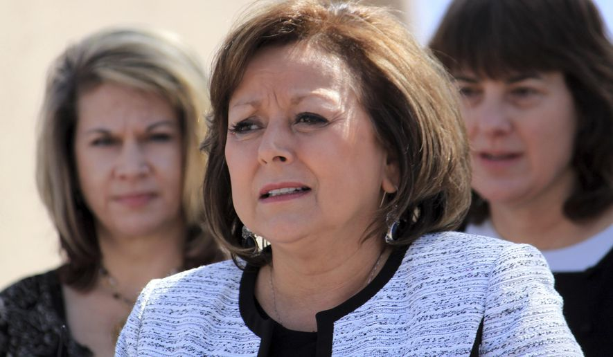 New Mexico Gov. Susana Martinez is flanked by advocates as she talks about opioid and heroin overdoses in New Mexico during a bill signing ceremony at a substance abuse treatment center in Albuquerque, N.M., on Thursday, April 6, 2017. Among other things, the bill signed by Martinez requires all state and local law enforcement officers to be equipped with an overdose antidote kit. (AP Photo/Susan Montoya Bryan)