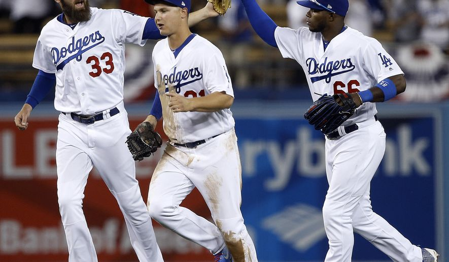 Los Angeles Dodgers left fielder Scott Van Slyke (33) and right fielder Yasiel Puig (66) celebrate with center fielder Joc Pederson after the Dodgers defeated the San Diego Padres 3-1 in a baseball game in Los Angeles, Wednesday, April 5, 2017. (AP Photo/Alex Gallardo)