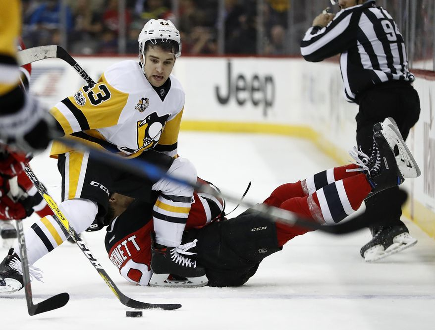 New Jersey Devils right wing Beau Bennett, bottom, is knocked down by Pittsburgh Penguins left wing Conor Sheary (43) while competing for the puck during the second period of an NHL hockey game, Thursday, April 6, 2017, in Newark, N.J. (AP Photo/Julio Cortez)