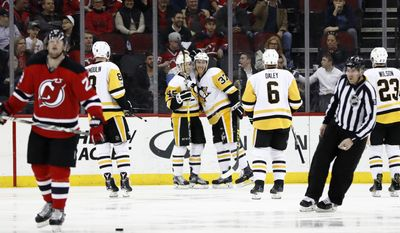 Pittsburgh Penguins celebrate a goal by Josh Archibald (45) against the New Jersey Devils during the second period of an NHL hockey game, Thursday, April 6, 2017, in Newark, N.J. (AP Photo/Julio Cortez)