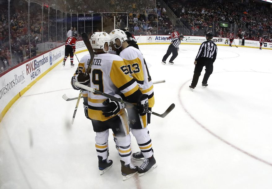 Pittsburgh Penguins players, from left, Josh Archibald (45), Jake Guentzel (59) and Nick Bonino (13) celebrate Guentzel's goal against the New Jersey Devils during the first period of an NHL hockey game, Thursday, April 6, 2017, in Newark, N.J. (AP Photo/Julio Cortez)