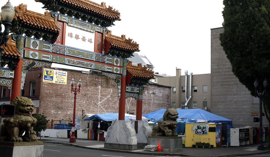 FILE - In this Oct. 4, 2013 file photo, the Right 2 Dream Too homeless camp stands next to the Chinatown gate in Portland, Ore. The camp, which has been at the entrance to Chinatown since 2011 was recently given an eviction notice. It will move to a piece of city-owned land between the Willamette River and Moda arena that's home to the Portland Trail Blazers NBA basketball team. Mayor Ted Wheeler said Thursday, April 6, 2017, that the move will be completed within 60 days. (AP Photo/Don Ryan, File)