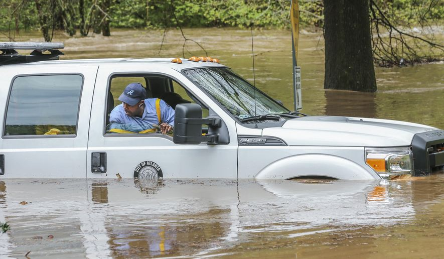 "An Atlanta Public Works crew is caught in the Peachtree Creek overflow onto the flooded Woodward Way as they were delivering Road Block equipment and had to be rescued by the Atlanta Fire Rescue's Swift Water Dive Team in Atlanta, Wednesday, April 5, 2017. Severe storms raking the Southeast unleashed one large tornado and more than a half dozen apparent twisters Wednesday, toppling trees, roughing up South Carolina's ""peach capital"" and raining out golfers warming up for the Masters. (John Spink/Atlanta Journal-Constitution via AP)"