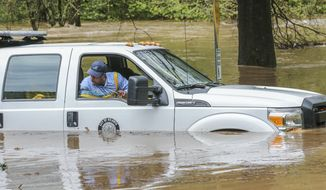 """An Atlanta Public Works crew is caught in the Peachtree Creek overflow onto the flooded Woodward Way as they were delivering Road Block equipment and had to be rescued by the Atlanta Fire Rescue's Swift Water Dive Team in Atlanta, Wednesday, April 5, 2017. Severe storms raking the Southeast unleashed one large tornado and more than a half dozen apparent twisters Wednesday, toppling trees, roughing up South Carolina's """"peach capital"""" and raining out golfers warming up for the Masters. (John Spink/Atlanta Journal-Constitution via AP)"""