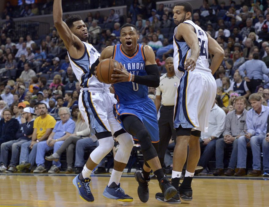 Oklahoma City Thunder guard Russell Westbrook (0) drives between Memphis Grizzlies guard Andrew Harrison, left, and forward Brandan Wright during the first half of an NBA basketball game Wednesday, April 5, 2017, in Memphis, Tenn. (AP Photo/Brandon Dill)