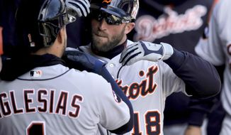 Detroit Tigers' Tyler Collins (18) celebrates with teammate Jose Iglesias (1) in the dugout after hitting a solo home run during the second inning of a baseball game against the Chicago White Sox Thursday, April 6, 2017, in Chicago. (AP Photo/Paul Beaty)