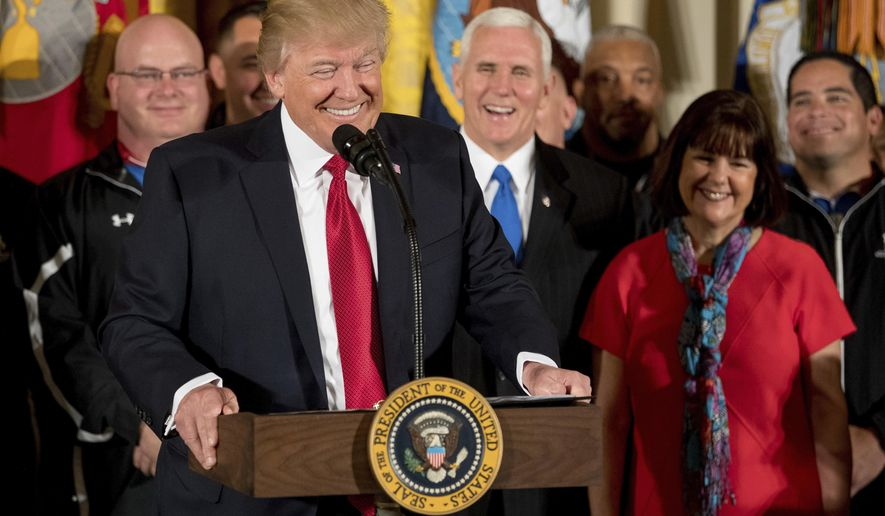 President Donald Trump, accompanied by Vice President Mike Pence his wife Karen, right, and others, smiles while speaking at a Wounded Warrior Project Soldier Ride event in the East Room of the White House in Washington Thursday, April 6, 2017. (AP Photo/Andrew Harnik)