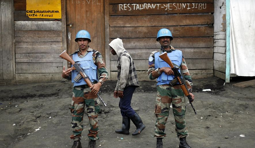 FILE - In this Friday Nov. 30, 2012 file photo, Two UN soldiers stand guard in Goma, Democratic Republic of Congo. Part of President Donald Trump's proposed deep budget cuts in foreign aid could be significant reductions in U.N. peacekeeping missions in some of the world's most dangerous places. On Thursday, April 6, 2017 the U.N. Security Council meets on the issue at the United States' request. (AP Photo/Jerome Delay File)