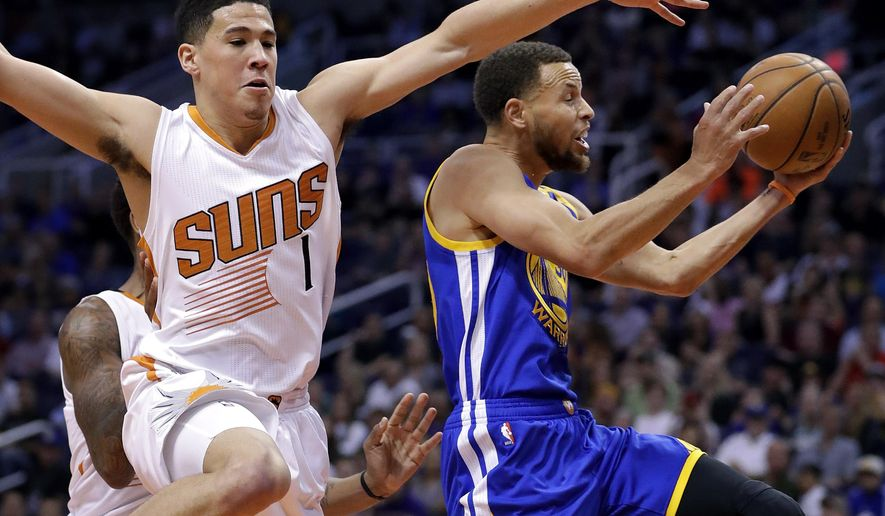 Golden State Warriors guard Stephen Curry drives past Phoenix Suns guard Devin Booker (1) during the first half of an NBA basketball game, Wednesday, April 5, 2017, in Phoenix. (AP Photo/Matt York)