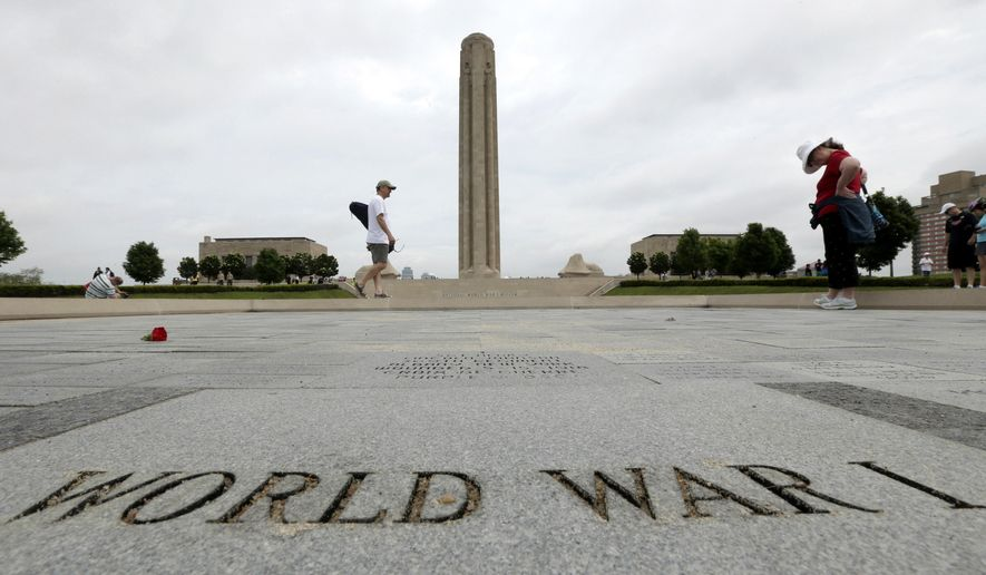 """FILE - In this May 26, 2014 file photo, visitors look at memorial bricks after a Memorial Day observance at the National World War Museum at Liberty Memorial in Kansas City, Mo. Foreign dignitaries from around the globe are converging on Kansas City, Missouri, and its towering World War I monument to observe the centennial of the day the U.S. entered """"The Great War."""" A sellout gathering of 3,000 onlookers also have snapped up tickets for the daylong observance Thursday, April 6, 2017,  titled """"In Sacrifice for Liberty and Peace."""" (AP Photo/Charlie Riedel, File)"""