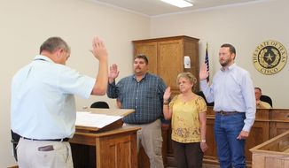 Judge Walker administers the oath of office to Jason Weger, Sharon Wilcoxen and James King (2013). Photo courtesy of MicroplexNews.com.