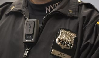 In this Dec. 3, 2014, file photo, New York Police Department officer Joshua Jones wears a VieVu body camera on his chest during a news conference in New York. The NYPD, the nation's largest police department, will begin rolling out body cameras by the end of this month, after resolving the thorniest issues on when to turn them on and off, and how long video will be kept. (AP Photo/Mark Lennihan, File)