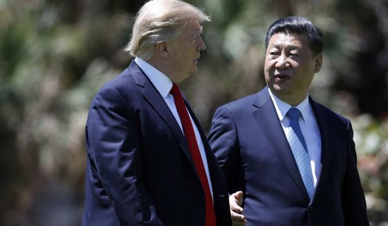 President Donald Trump and Chinese President Xi Jinping walk together after their meetings at Mar-a-Lago, Friday, April 7, 2017, in Palm Beach, Fla. Trump was meeting again with his Chinese counterpart Friday, with U.S. missile strikes on Syria adding weight to his threat to act unilaterally against the nuclear weapons program of China's ally, North Korea. (AP Photo/Alex Brandon)